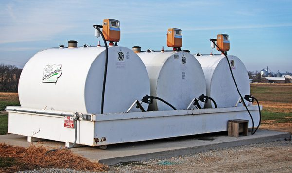 An outdoor containment dike holding three fuel storage tanks with pumps